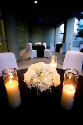 """Mass of white carnations in a 4"""" clear glass cube are flanked by 8"""" candles to accent an outdoor guest table.  Modern Design - Low Carnation Centerpiece"""