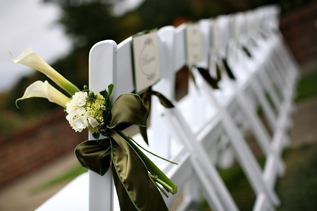 Green and White Hydrangea, Green Hypericum Berries, and White Calla Lilies tied with an Apple Green Satin Ribbon accent the aisle chairs.  Green and White Aisle Decor