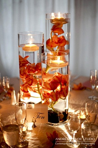 "Cluster of Submerged Cymbidium Orchid.  Orange cymbidium orchid stems submerged in 24"", 20"", and 16"" clear cylinder vases."