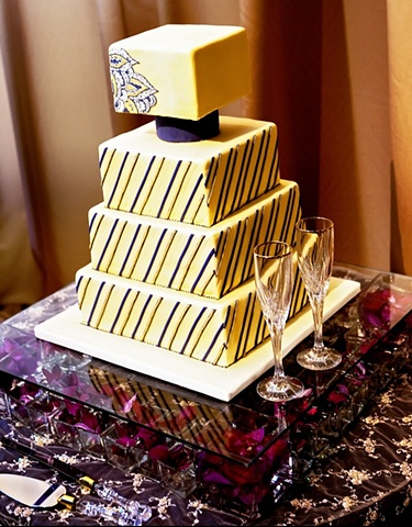 "Cake balnced on a clear, glass sheet supported by 2"" clear glass cubes, each containing a single rose bloom, and arranged in a geometric pattern."