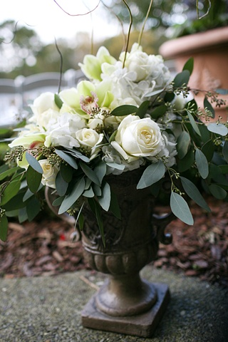 Large Rustic Urn composed of White Hydrangea, White Polo Roses, Green Cymbidium Orchids, and Seeded Eucalyptus.  Lush Entrance Decor in a Rustic Urn