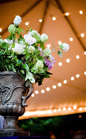 Lush Buffet Arrangement composed of green viburnum, purple hydrangea, and white roses in a rustic urn. Stacey Bode Photography