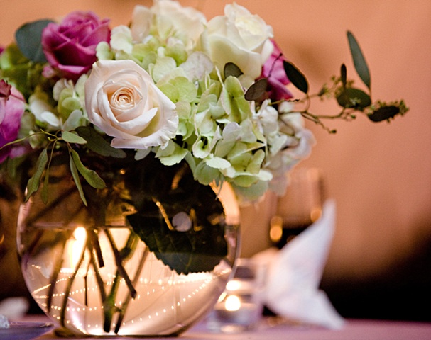 "Stacey Bode Photography Garden centerpiece composed of green hydrangeas, seeded eucalyptus, and lavender and white roses in an 8"" clear, glass globe vase."