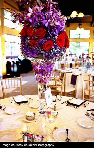 """Jaxon Photography Mass of red roses, and purple hydrangeas, purple mokara orchids, and curly willow in a clear, glass """"Reversible Vase"""" containing submerged purple mokara orchid blooms."""