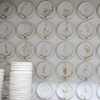 """A grid of coffee cup lids neatly arrayed on the studio wall creates an oddly organized counterpoint to the random spillage""."