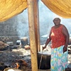 Woman cooking in tent city, photo from Zanmi Lakay workshop