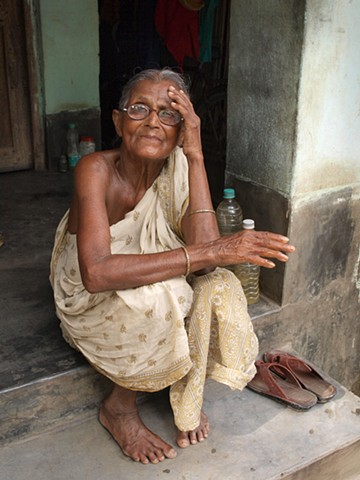 Elderly village woman on step