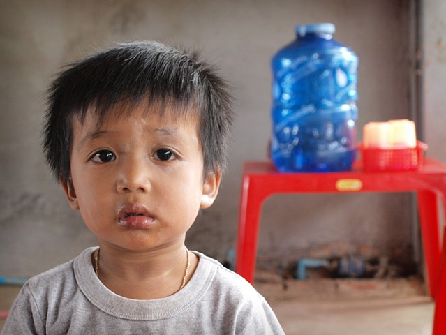 Toddler in his village home, which doubles as a shop