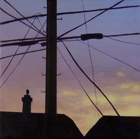 Sunset of telephone pole, wires, houses.