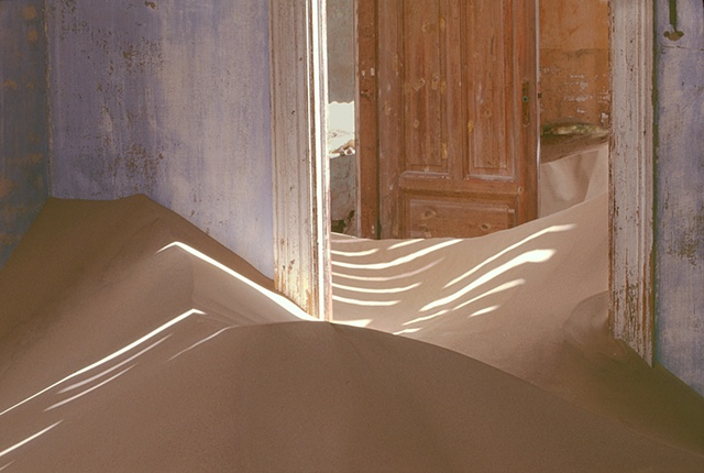 Kolmanskop Namibia, a deserted diamond mining town in the desert, blue walls with lathe strips on the ceiling making shadow patterns in the sand dunes in the room