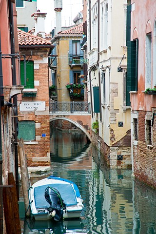 Quiet Scene of tranquil waters in the Venice Canal, flower boxes and window shutters