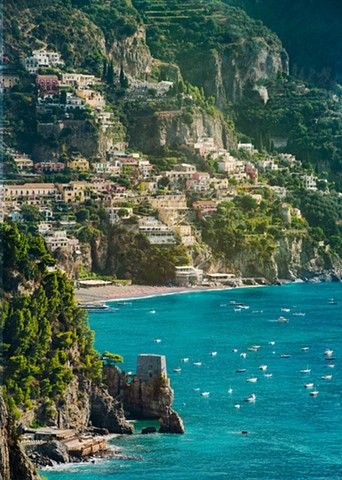 A morning glow lighting up the hills and houses of Positano above the turquoise waters