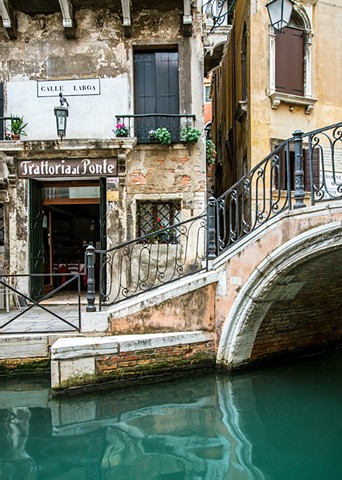 Along the Canal by the Bridge, emerald and turquoise colors in the Venice canal, tranquil reflections