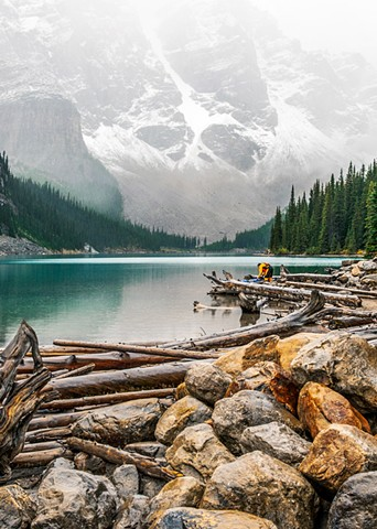 Moraine Lake in Banff National Park, yellow kayaker with mountain mists and snow cover