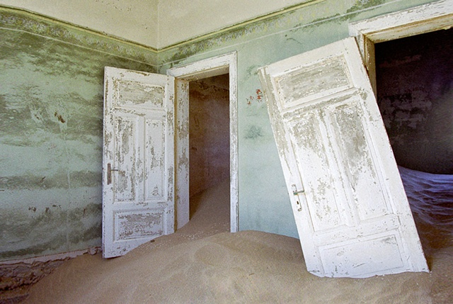 Kolmanskop Namibia deserted diamond mining town in the desert, sand is taking over, green painted walls and doors hanging off hinges, sand dunes