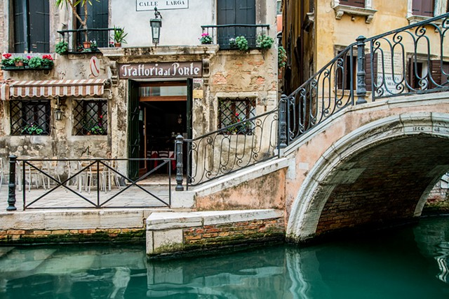 Trattoria by the Canal in Venice, emerald and turquoise colors in the Venice canals, tranquil reflections