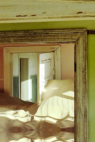 Kolmanskop Namibia, a deserted diamond mining town in the desert, soft green room looking into pink and out to the hallway, sand dunes in the room