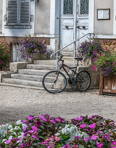 Bicycle and purple and pink flowers  with Old French Architecture