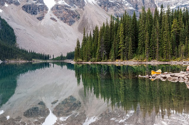 Reflections on Moraine Lake with a yellow canoe resting at the side