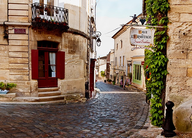 St Emilion France cobblestone street curves around a medieval building, vines and sign Cave de L'Ermitage