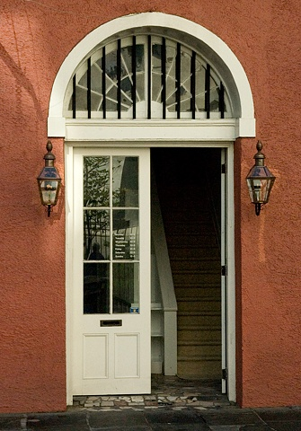 Open door to rust colored stucco house with gas lamps in New Orleans
