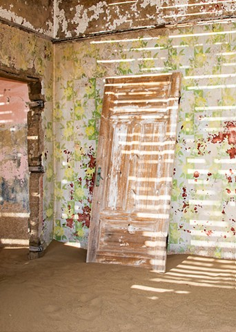 Shadow Patterns on the walls play on the flowered wallpaper and the old door.