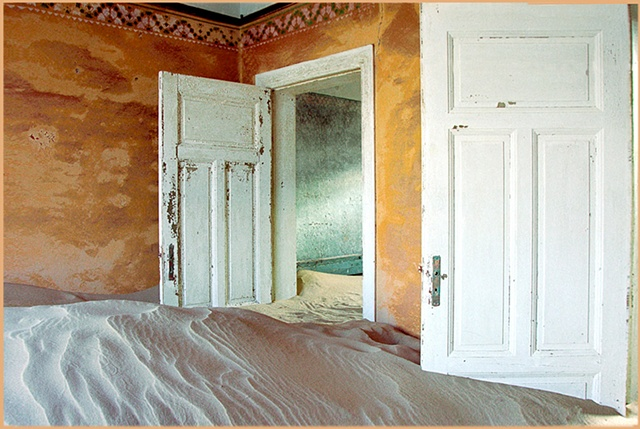 Kolmanskop Namibia, a deserted diamond mining town in the desert, colorful yellow walls, open doors hanging off their hinges,