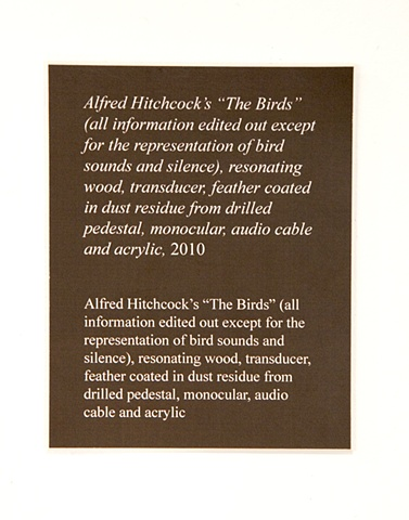 "title: Alfred Hitchock's ""The Birds"" (all information edited out except for the representation of bird sounds and silence), resonating wood, transducer, feather coated in dust residue from drilled pedestal, monocular, audio cable and acrylic"