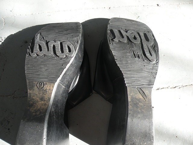 "Carved shoes with the words ""you"" and ""and"" on the soles. By Courtney Kessel"