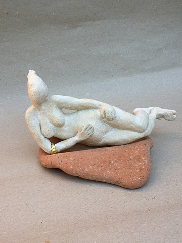 A small figurine, wearing a gold leaf bangle, sitting on a washed down ceramic tile, found on a beach