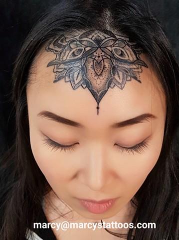 mandala forehead tattoo