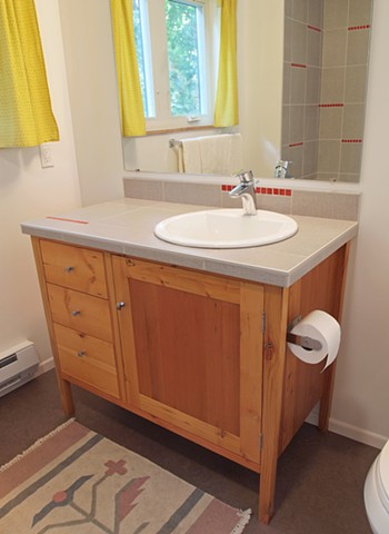 Handmade bath vanity from salvaged reclaimed wood with tile top.