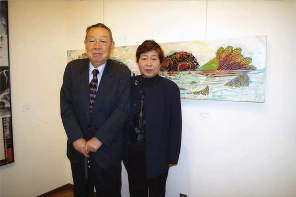 Dr. and Mrs. Saito with Kathleen King's paintings.
