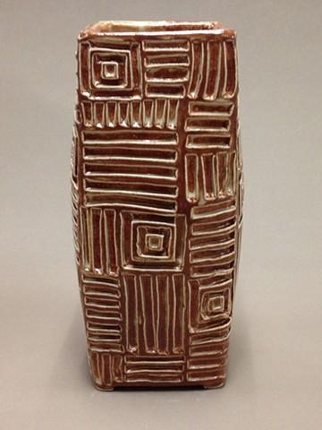 hand carved stoneware vase with geometric pattern under cream-tan glaze
