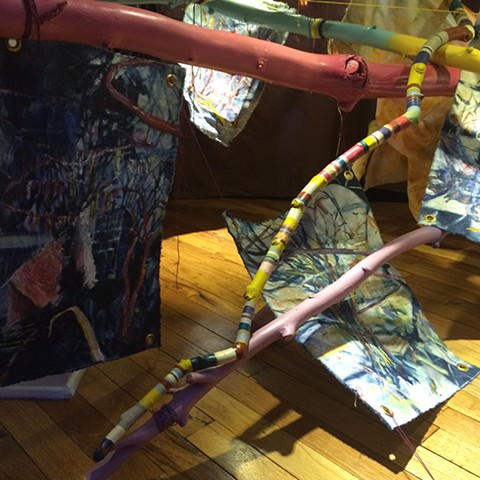 Brightly painted sticks crossing each other, providing hanging system for unstretched oil paintings on indigo dyed canvas, all installed in the back space of a 1991 Ford Bronco