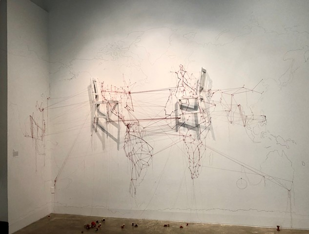 An installation reflecting on the overwhelming scale of displacement and migration in the present day. A hand-drawn map and researched routes most often traveled are indicated with extended red threads across territories, both watery and earthen.  Relocat