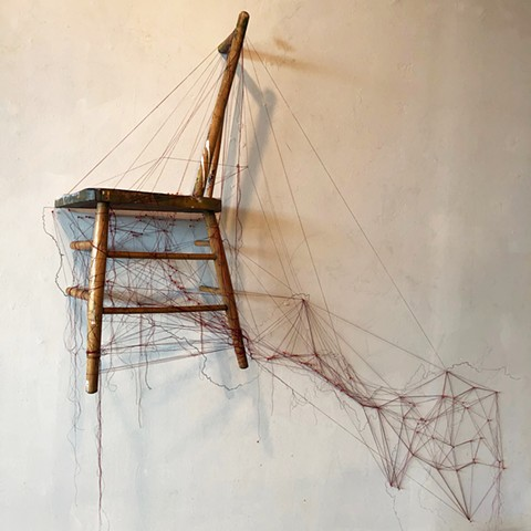 Half of a chair is secured to the wall on top of a graphite drawing of a map of the world.  Red threads and map pins trace current migration paths.