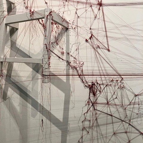 Detail of an installation about migrations completed at the San Francisco Arts Commission Gallery.  A large map of the world was drawn on the wall in graphite, map pins and red thread trace the paths of current major migrations.