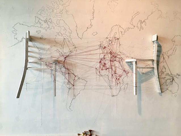Thread from point to point on a map of the world traces major current movements of people.  A chair is split in half and secured to the wall on top of the graphite map of the world.