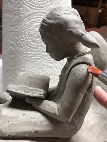 Carving out details on wet clay.