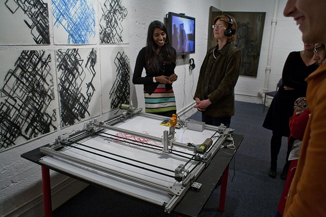 "Santhi Elayaperumal demonstrating ""RedGreenBrain"" her brainwave-driven robotic drawing machine"