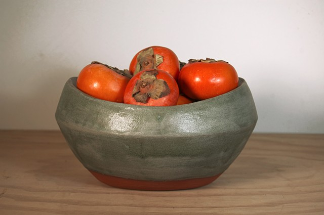 persimmons in green bowl