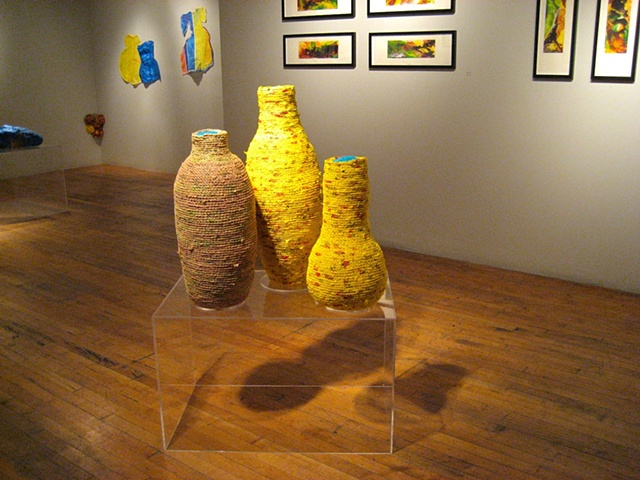Closer photo of vessels with other works in the background.