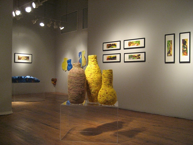 Closer view of three vessels in the space with paintings in the background.