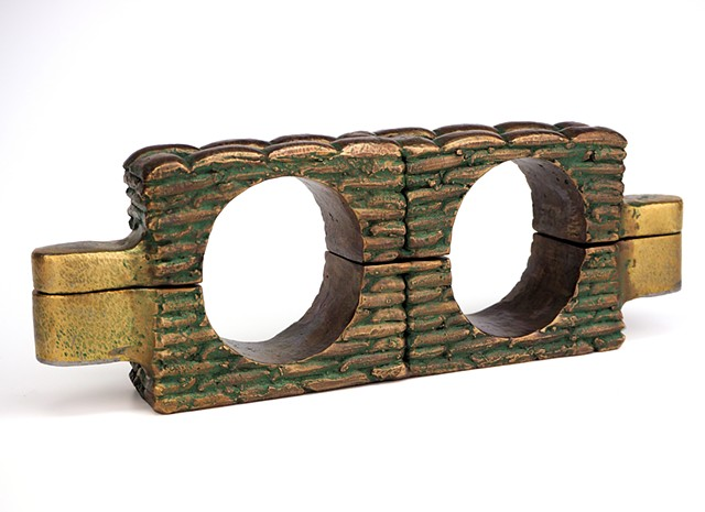 Fully functional cast bronze sandbag-stack shackle stocks with double lock mechanism.
