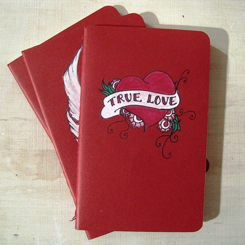 traditional tattoo design of a red heart with true love written across it, on an original red Moleskine Cahier notebook. By Brighton painter Linda Boucher
