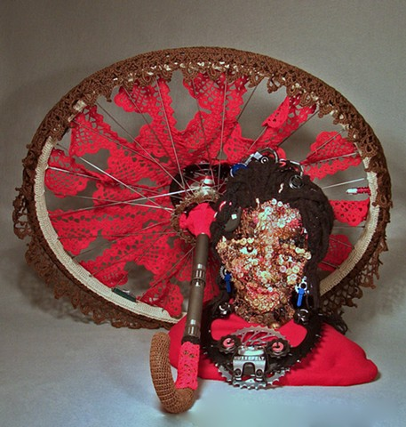 Mixed media sculpture of African girl in buttons and crochet with Bicycle wheel by Marie Bergstedt