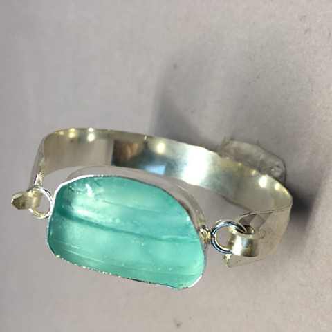 sterling silver cuff with light aqua piece of seaglass which was once a bottle top