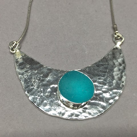 Brilliant aqua piece of seaglass set on hand hammered fine silver half moon.