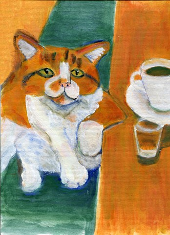 Orange and white tabby next to a cup of coffee and a shotglass.